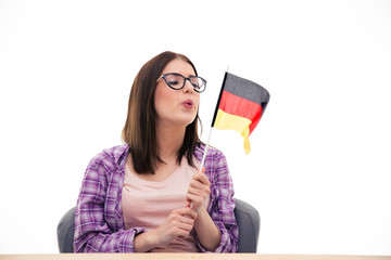 Young woman blowing on the German flag