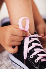 Closeup on child hands as they tie shoes-shallow depth of field