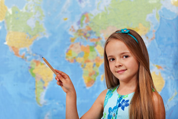 Little student girl pointing to blurry world map