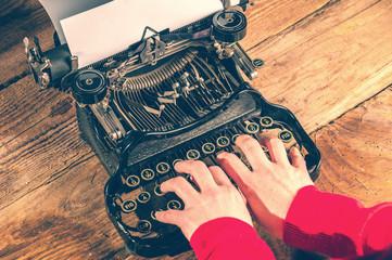 Hands secretary, writing on an old typewriter.