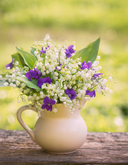 Beautiful bouquet of lilies of the valley and violets
