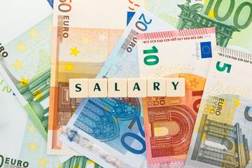 Several euro banknotes salary text dice