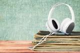 Fototapety Vinyl. Golden headphones lying on the stack of vinyle records.