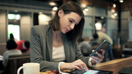 businesswoman comparing data on tablet  and smartphone in cafe