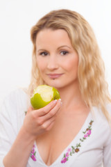 blurred face of young woman biting an apple