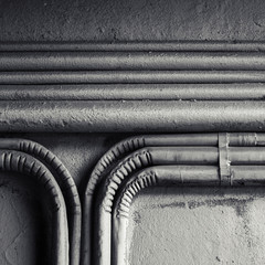 Electrical conduits mounted on old concrete wall