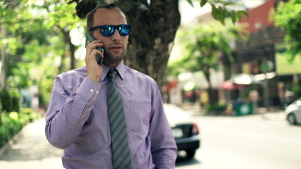 businessman talking on cellphone standing by street in city