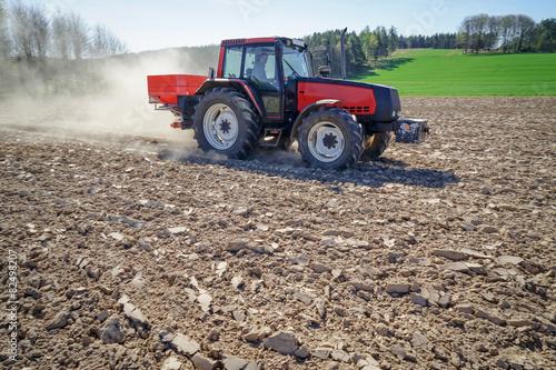 Getreideanbau, Landwirt beim Düngerstreuen auf Feld - 82498207