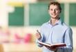 English. Young teacher near chalkboard in school classroom
