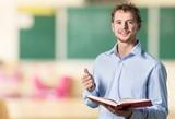 Fototapety English. Young teacher near chalkboard in school classroom