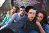 Fototapety Group of four teenage friends posing for a selfie