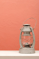 Old vintage lantern on white table in front of pink, coral wall