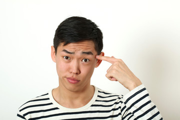 Funny young Asian man pointing his index finger against his temp