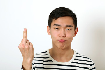 Displeased young Asian man giving the middle finger sign and loo