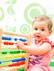 Baby spielt mit einem Rechenschieber