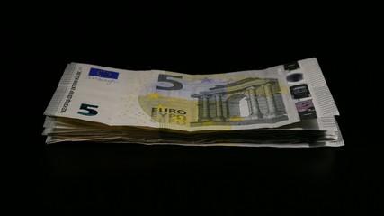 Stack of 5 euro bills turning