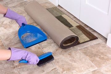 Image with a rolled rug and broom with dustpan