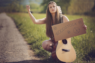 Beautiful hippie hitch-hiker with guitar