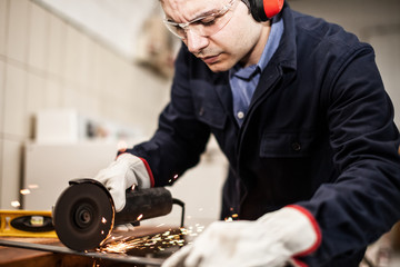 Worker using a grinder in a factory