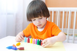 Little boy playing with wax pencils