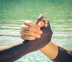 Black and white hands handshake against racism