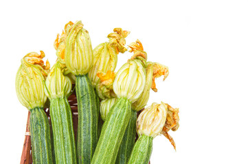 Courgettes with flowers in brown basket isolated