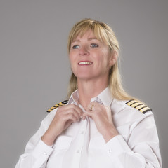Woman airline officer buttoning white uniform shirt