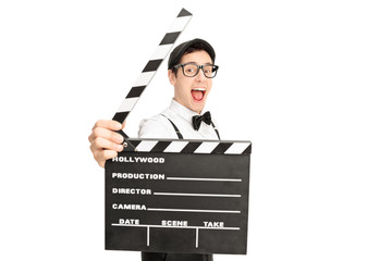 Excited movie director posing behind a clapperboard