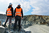 Two workers and quarry in background