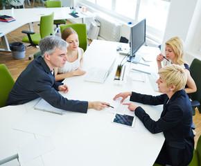 Team diskutiert am Schreibtisch beim Meeting