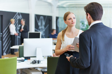 Mann und Frau im Büro reden miteinander
