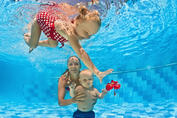 Baby underwater swimming lesson with instructor in the pool