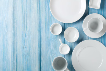 Empty plates and bowls on blue wooden background