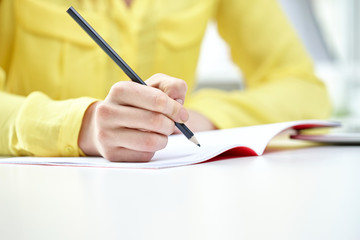 close up of female hands writing to notebook