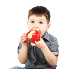 Close-up portrait of a little boy eating red apple