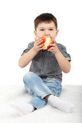 Little boy eating a red apple