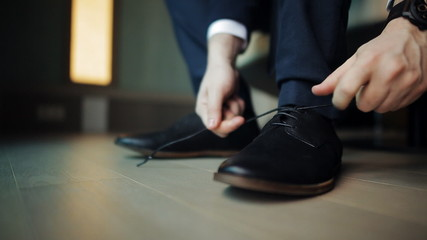 man tying the laces on black boots