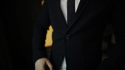 groom window buttoning his jacket