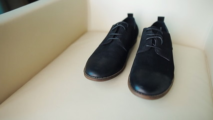 men's shoes on a leather chair