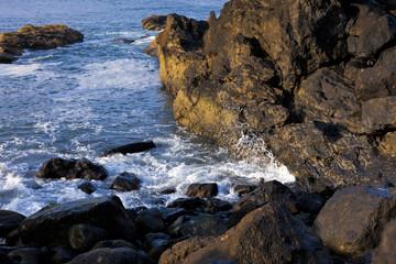 Waves crash into rocks.