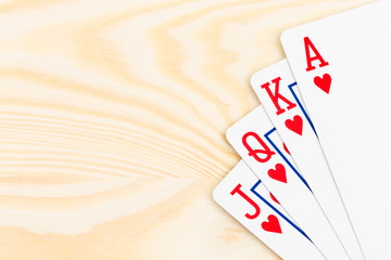 Royal flush poker playing cards on wooden background