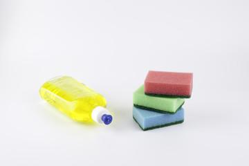Dishwashing liquid with a sponge on white background