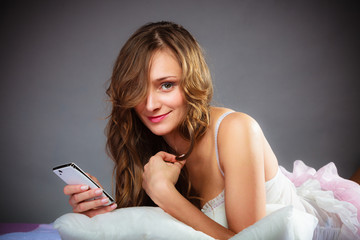 Woman on bed holding mobile phone.