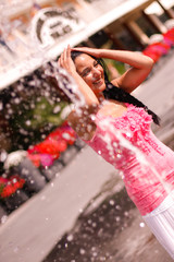Junge Frau genießt Abkühlung am Brunnen