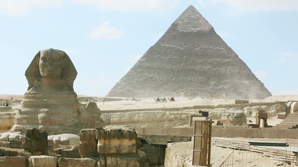 Tourists rides camels between Sphinx and Khafre's pyramid