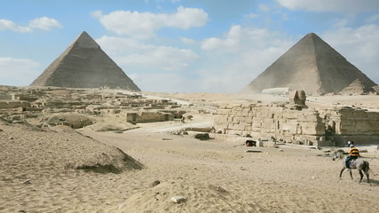 Tourists rides camels at the pyramids, Giza Necropolis