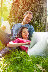 A nice couple sitting in the grass, using a laptop