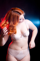 Overweight girl in lijerie on black background with two lights b