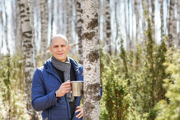 man holding a mug in forest