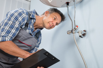 Plumber With Clipboard Looking At Electric Boiler